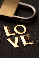 represented - Single word 'love' in gold lettering beside padlock Stock Photo - Premium Royalty-Freenull, Code: 653-06534357