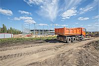 Dumper truck parked on dirt track at construction site Stock Photo - Premium Royalty-Freenull, Code: 653-06534525