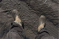 Construction worker's feet in mud of tyre track Stock Photo - Premium Royalty-Freenull, Code: 653-06534528