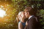 A well-dressed couple kissing in a park