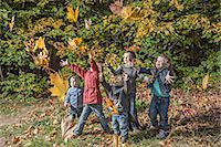 Five kids trying to catching falling autumn leaves Stock Photo - Premium Royalty-Freenull, Code: 653-06534754