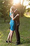 An elegantly dressed man kissing his girlfriend passionately while squeezing her bottom