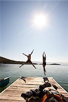 Man and woman jumping off end of dock. Stock Photo - Premium Royalty-Freenull, Code: 6106-06535889