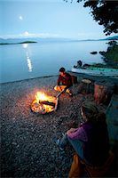 Man and woman by campfire at night on lake shore. Stock Photo - Premium Royalty-Freenull, Code: 6106-06535892
