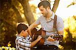 Father and son playing guitar together