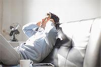 Man listening to headphones on sofa Stock Photo - Premium Royalty-Freenull, Code: 614-06536756