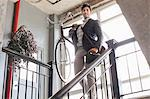 Man carrying bicycle down staircase Stock Photo - Premium Royalty-Free, Artist: ableimages, Code: 614-06536793