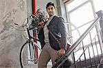 Man carrying bicycle down staircase Stock Photo - Premium Royalty-Free, Artist: Sheltered Images, Code: 614-06536794