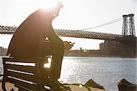 people sitting on bench - Man using cell phone by urban bridge Stock Photo - Premium Royalty-Freenull, Code: 614-06536806