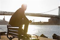 people sitting on bench - Man using cell phone by urban bridge Stock Photo - Premium Royalty-Freenull, Code: 614-06536807