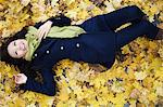 Woman laying in autumn leaves Stock Photo - Premium Royalty-Free, Artist: CulturaRM, Code: 614-06536866