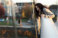Woman leaning over bridge railing Stock Photo - Premium Royalty-Freenull, Code: 614-06536870