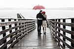 Couple kissing on wooden pier in rain Stock Photo - Premium Royalty-Free, Artist: I Dream Stock, Code: 614-06536901
