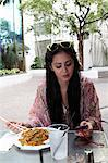 Woman using cellphone and eating Stock Photo - Premium Royalty-Free, Artist: ableimages, Code: 614-06536906