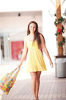 Woman carrying shopping bag in mall Stock Photo - Premium Royalty-Freenull, Code: 614-06537150