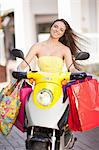 Woman carrying shopping bags on scooter Stock Photo - Premium Royalty-Free, Artist: Cultura RM, Code: 614-06537152