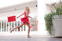 Woman carrying shopping bag outdoors Stock Photo - Premium Royalty-Freenull, Code: 614-06537163