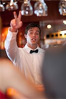 Waiter offering more drinks at bar Stock Photo - Premium Royalty-Freenull, Code: 614-06537213