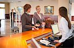 Businesswoman checking in to hotel Stock Photo - Premium Royalty-Free, Artist: Blend Images, Code: 614-06537249