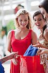 Women looking in shopping bag Stock Photo - Premium Royalty-Free, Artist: Blend Images, Code: 614-06537295