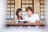 Couple reading travel book together Stock Photo - Premium Royalty-Freenull, Code: 614-06537382