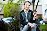 Woman using cell phone in urban park Stock Photo - Premium Royalty-Free, Artist: Ikon Images, Code: 614-06537510