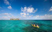 People rowing canoe in tropical water Stock Photo - Premium Royalty-Freenull, Code: 614-06537524