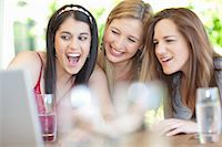 Smiling women using laptop together Stock Photo - Premium Royalty-Freenull, Code: 614-06537611