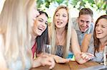 Group of friends talking at table Stock Photo - Premium Royalty-Free, Artist: Ikon Images, Code: 614-06537613