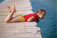 young girl lying on wooden pier Stock Photo - Premium Royalty-Freenull, Code: 618-06538614