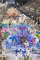 South America, Rio de Janeiro, Rio de Janeiro city, costumed dancer in a feather headdress and the floats and dancers of the Caprichosos samba school at carnival in the Sambadrome Marques de Sapucai Stock Photo - Premium Rights-Managednull, Code: 862-06540936
