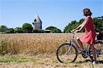 France, Charente Maritime, Ile de Re.  A tourist cycling on one of the many cycle paths that criss crosses the island stops to look at an old converted windmill outside the village of Ars en Re. MR Stock Photo - Premium Rights-Managed, Artist: AWL Images, Code: 862-06541443