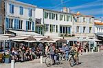 France, Charente Maritime, Ile de Re.  Tourists eat at tables set outside the cafes and restaurants that overlook the small harbour in La Flotte. Stock Photo - Premium Rights-Managed, Artist: AWL Images, Code: 862-06541469
