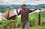 A jovial fisherman with fishing baskets and his catch of the day, which he caught in Lake Mutanda, Uganda, Africa Stock Photo - Premium Rights-Managed, Artist: AWL Images, Code: 862-06543269