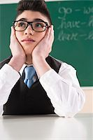 Boy Leaning on Hands in front of Chalkboard in Classroom Stock Photo - Premium Royalty-Freenull, Code: 600-06543516