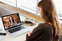 Woman in library using a laptop to have a video chat with her friend Stock Photo - Premium Rights-Managednull, Code: 700-06553290