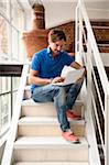 Young man sitting on a stairs at home working with laptop computer Stock Photo - Premium Rights-Managed, Artist: Siephoto, Code: 700-06553386