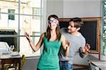 Couple playing blind man's buff in restraurant Stock Photo - Premium Rights-Managed, Artist: Siephoto, Code: 700-06553387