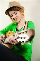 Portrait of Teenage Girl Wearing Hat and Playing Acoustic Guitar, Studio Shot on White Background Stock Photo - Premium Royalty-Freenull, Code: 600-06553416