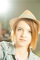 Head and shoulders portrait of teenage girl wearing hat in studio. Stock Photo - Premium Royalty-Freenull, Code: 600-06553545