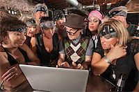 Group of impressed biker gang members watching nerd using a computer Stock Photo - Royalty-Freenull, Code: 400-06557766