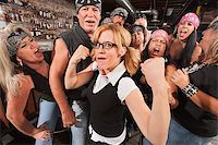 Cute female nerd flexing muscles with gang of bikers Stock Photo - Royalty-Freenull, Code: 400-06557772