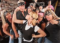 Biker gang cheering on skinny female nerd flexing muscles Stock Photo - Royalty-Freenull, Code: 400-06557773