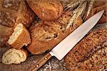 A selection of bread loaves with knife on wood table Stock Photo - Royalty-Free, Artist: Sandralise                    , Code: 400-06558229