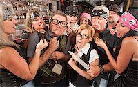Biker gang mugging scared nerd couple in bar Stock Photo - Royalty-Freenull, Code: 400-06558605