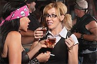 Blond woman and biker gang lady talking while smoking and drinking Stock Photo - Royalty-Freenull, Code: 400-06558615