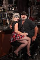Happy middle aged motorcycle gang couple sitting at bar counter Stock Photo - Royalty-Freenull, Code: 400-06558622