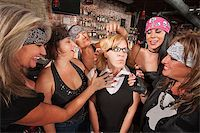 Female motorcycle gang touching a frightened nerd Stock Photo - Royalty-Freenull, Code: 400-06561342