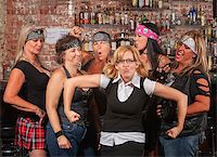 Female motorcycle gang laughing at nerd in bar Stock Photo - Royalty-Freenull, Code: 400-06561344