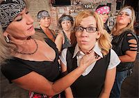Tough biker gang woman with hand near female nerd's neck Stock Photo - Royalty-Freenull, Code: 400-06561348